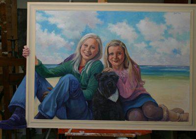 Twee kinderen met een hond op strand